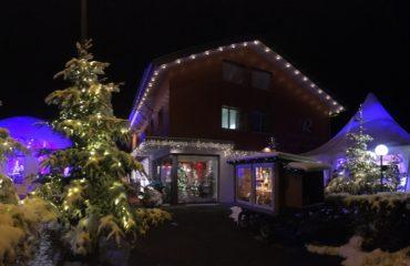 Stimmungsvolle Weihnachtsszene in der Nacht mit beleuchtetem Chalet und Tannenbaum